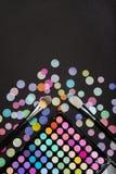Косметическая предпосылка с щетками макияжа и палитра теней для век на черной предпосылке с разбросанным confetti стоковые изображения rf