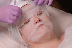 Косметическая процедура Маска для стороны Женщина с глазами закрыла Руки Beautician в розовых перчатках Концепция подмолаживания  стоковые фото