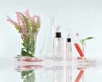 Косметические контейнеры бутылки с зелеными травяными листьями и научным стеклоизделием, пустым пакетом ярлыка для клеймя модель- стоковое фото rf