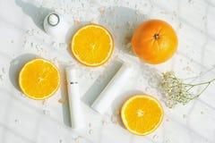 Косметические контейнеры бутылки насоса пены с свежими оранжевыми кусками, пустым ярлыком для клеймя модель-макета, естественного Стоковые Фотографии RF