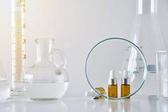 Косметические коричневые контейнеры бутылки и научное стеклоизделие, фокус на пустом пакете ярлыка для клеймя модель-макета Стоковые Фотографии RF