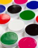 Косметические круглые опарникы, пестротканая краска стороны, белая предпосылка, аппаратуры художника Стоковая Фотография