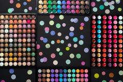 Косметические палитры макияжа с разбросанным красочным confetti на черной предпосылке стоковое фото