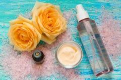 Косметические продукты от подняли, сливк и бутылка розовой воды, эфирного масла, цветков на предпосылке бирюзы деревянной Стоковое Изображение RF
