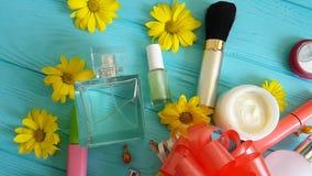Косметический состав сумки с декоративными косметиками обхватывает на голубых деревянных цветках, духах акции видеоматериалы