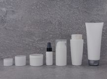 Косметический упаковывая набор на серой предпосылке группа в составе масло сыворотки сливк skincare продукт спа лицевой красоты к стоковые изображения