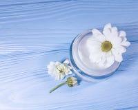Косметический cream продукт в стеклянной предпосылке белых цветков опарника голубой деревянной Стоковые Изображения