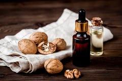 Косметическое и терапевтическое масло грецкого ореха на темной деревянной предпосылке Стоковые Изображения RF