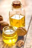 Косметическое и терапевтическое масло грецкого ореха на деревянной предпосылке Стоковые Изображения