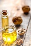 Косметическое и терапевтическое масло грецкого ореха на деревянной предпосылке Стоковые Изображения RF