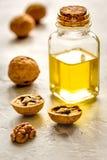 Косметическое и терапевтическое масло грецкого ореха на серой предпосылке Стоковые Фото