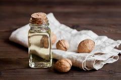 Косметическое и терапевтическое масло грецкого ореха на темной деревянной предпосылке Стоковые Изображения