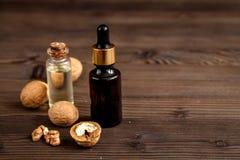 Косметическое и терапевтическое масло грецкого ореха на темной деревянной предпосылке Стоковая Фотография