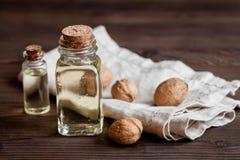 Косметическое и терапевтическое масло грецкого ореха на темной деревянной предпосылке Стоковое Изображение RF
