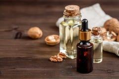 Косметическое и терапевтическое масло грецкого ореха на темной деревянной предпосылке Стоковые Фото