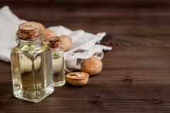 Косметическое и терапевтическое масло грецкого ореха на темной деревянной предпосылке Стоковое Фото