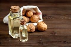 Косметическое и терапевтическое масло грецкого ореха на темной деревянной предпосылке Стоковые Фотографии RF