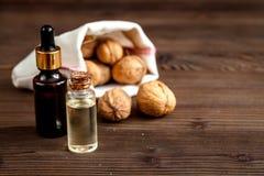 Косметическое и терапевтическое масло грецкого ореха на темной деревянной предпосылке Стоковое фото RF