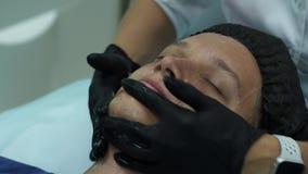 Косметология людей s Молодой мужчина получая лицевые процедуры на клинике красоты Слезать кожу сток-видео