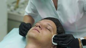 Косметология людей s Молодой мужчина получая лицевые процедуры на клинике красоты Слезать кожу акции видеоматериалы