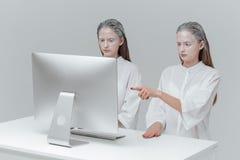 2 космических женщины сидя на компьютере Стоковые Изображения