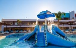 Космос бассейном с спортивной площадкой loungers и детей солнца с скольжениями Стоковые Изображения RF