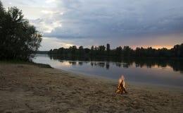 Костер на банке реки на заходе солнца Стоковые Фото