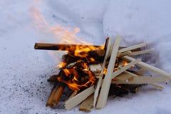 Костер на белом снеге в зиме, огне и обломоках Стоковые Изображения
