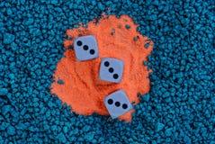 3 кости игры на красном песке и голубых камнях Стоковые Изображения RF