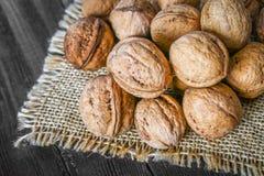 Косточки раковины и грецкого ореха на коричневом деревянном столе Стоковая Фотография RF