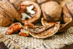 Косточки раковины и грецкого ореха на коричневом деревянном столе Стоковые Фото