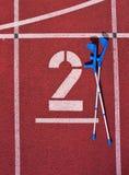 Костыль медицины на номер два Большой белый номер следа на красной резиновой беговой дорожке Gentle текстурированные идущие бегов Стоковое Изображение RF