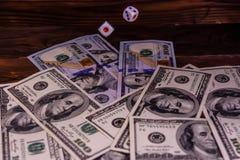 Кость в полете над 100 долларовыми банкнотами Азартная игра conc Стоковые Фото