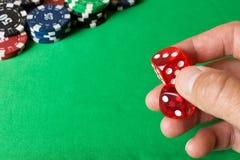 Кость в человеческой руке против зеленой таблицы и покера c Стоковое Изображение RF