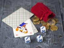 Кость, играя карточки и красная сумка денег на деревянном столе Стоковые Изображения RF