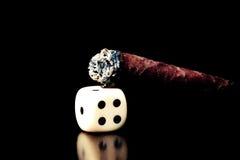 Кость и сигара одной белизны осветили на старой деревянной коричневой таблице Стоковое Фото