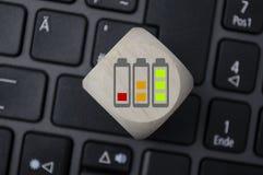 Кость куба с символами загрузки батареи стоковое изображение