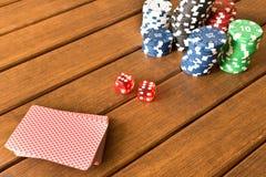 Кость, пакет перфокарт и обломоки на деревянном столе Играть в азартные игры, pok Стоковое Изображение