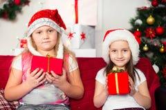2 костюма рождества девушек сидя на софе Стоковые Фотографии RF
