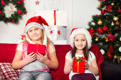 2 костюма рождества девушек сидя на софе Стоковое фото RF