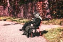 Костюмированные пары наслаждаются солнцем на стенде в парке во время стоковая фотография