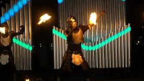 3 костюмы и маски парней сценарных одновременно танцуя с огнем на выставке огня видеоматериал