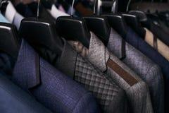 Костюмы людей на вешалках в других цветах стоковая фотография rf