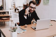 костюм бизнесмена s Говорить на телефоне проект Ноутбук стоковые фото