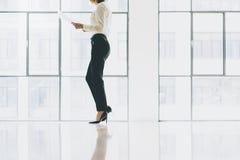 Костюм бизнес-леди фото крупного плана нося Офис просторной квартиры открытого пространства Держать руки бумаг Проанализируйте пл Стоковое фото RF