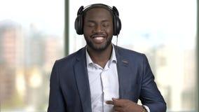 Костюм и наушники чернокожего человека нося, наслаждаясь музыкой видеоматериал