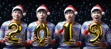 Костюм рождества человека нося держа золотой воздушный шар 2019 multi стоковая фотография rf