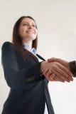 Костюм счастливой коммерсантки нося тряся мужскую руку, фокус на Хане Стоковое Изображение
