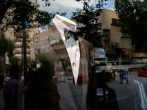 Костюм человека в витрине магазина отражает людей в улице Шоппинг стоковые фото