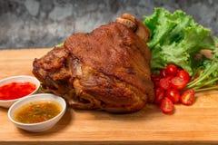 Костяшка свинины или немецкие hocks свинины с овощем и плодоовощ служили с соусом на прерывая доске и на деревянном столе стоковое фото rf